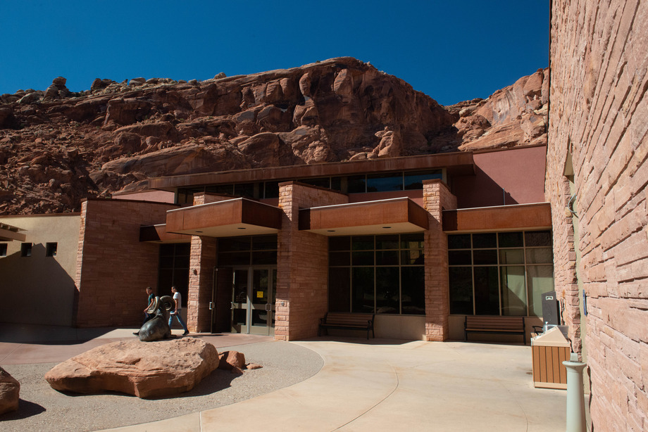 a brick building with large red rock cliffs above it