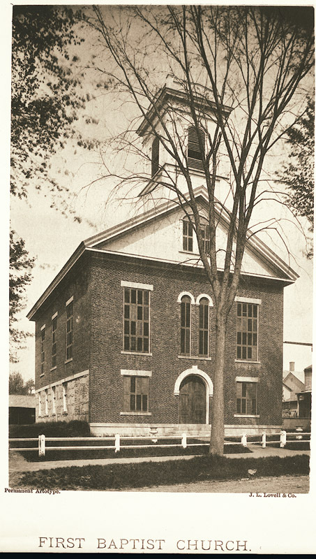 View of the First Baptist Church on South Pleasant Street with a white fence in the foreground.