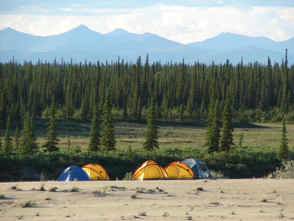 5 tents on the sand near forest and mountains.