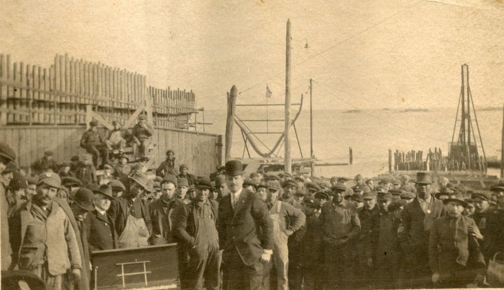 Shipbuilders standing as a group at the Noank Shipyard.