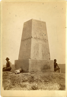 "View of the Monument on Custer Hill. LIBI_00312_11273; ONE ALBUMEN CABINET VIEW OF THE MONUMENT ON CUSTER HILL. ONE MAN AND A DOG TO THE LEFT, ONE MAN TO THE RIGHT. THE MONUMENT IS BADLY CHIPPED.; Album, Photograph;Courtesy of the National Park Service, Little Bighorn Battlefield National Monument, LIBI_00312_11273, Unknown Photographer, ""View of the Monument on Custer Hill,"" date unknown"