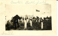 "People Among the Custer Group of Markers on Last Stand Hill. LIBI_00195_06971; Black and white photo postcard. This image depicts people scattered among the markers of the Custer Group on Last Stand Hill. The Custer Monument surrounded by an iron fence is visible in the background. A flag is at half-mast. A handwritten note along the top mount reads: ""Custer Battlefield"". The word ""Smith"" is written in pencil in the left corner of the mount. On verso, a pencil note reads: ""Custer Battlefield"".  The image was taken by an unknown photographer on an unknown date.  There are some stains on it. ; print, photographic; Courtesy of the National Park Service, Little Bighorn Battlefield National Monument, LIBI_00195_06971, Unknown Photographer, ""People Among the Custer Group of Markers on Last Stand Hill,"" date unknown."
