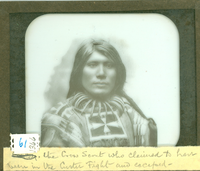 "An Unknown Native American [Wrongly Identified as Curly] Wearing a Bear-Claw Neckless. LIBI_00030_01366; A lantern-slide (glass transparency), ""Curly, Crow Scout""; A bust view of unidentified Indian. Note identifies it as curly, but definitely not. The individual wears a bear-claw neckless and a shirt decorated with beads. The handwritten note reads: ""the Crow Scout who claimed to have been in the Custer Fight and escaped-""  It was produced by unknown photographer, on unknown date.  [Bowen No. 61.]; transparency, latern-slide [photographic material];  Courtesy of the National Park Service, Little Bighorn Battlefield National Monument, LIBI_00030_01366, Unknown Photographer, ""An Unknown Native American [Wrongly Identified as Curly] Wearing a Bear-Claw Neckless,"" date unknown"