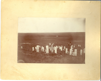 "The Custer Group with a Wooden Cross for George Armstrong Custer's Marker. LIBI_00300_10562; Black and white photograph mounted on cardboard. This image depicts the Custer grouping of markers with a wooden cross for George Custer. U.S. Flags have been placed on the markers. People are visible in the background. There is a small tear in the upper right corner of the cardboard and there are light brown stains throughout the mount. A handwritten note on the verso reads: ""Memorial Day, Custer Battlefield 1897 N Trall [?] Parrons"". The photo was taken by Mr. Krotzenberg in 1897. ; photograph; Courtesy of the National Park Service, Little Bighorn Battlefield National Monument, LIBI_00300_10562, Krotzenberg, ""The Custer Group with a Wooden Cross for George Armstrong Custer's Marker,"" 1897."