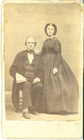 "Elizabeth Bacon Custer with Judge Bacon. LIBI_00295_10694; A Carte de vista mounted on a cardboard back; 2 1/8"" x 3 3/8""  from a albumen. The image depicts a portrait of Judge Bacon & Elizabeth Bacon Custer. Libby is standing. She is wearing striped dress with button from collar to waist. Her hair is parted in center. Her right arm is supported on Judge Bacon's shoulder. The portrait is a full view of face. Her left side and hands are visible; Libby is wearing white gloves. Judge Bacon is wearing a dark, three piece suit. The v-shaped vest is completely buttoned. The jacket has long tails. He also is wearing a white collar and dark tie. The image was taken by an unknown photographer, cira 1862. ; photograph;  Courtesy of the National Park Service, Little Bighorn Battlefield National Monument, LIBI_00295_10694, Unknown Photographer, ""Elizabeth Bacon Custer with Judge Bacon,"" circa 1892."