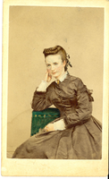 "A Colorized Photograph of Elizabeth Bacon Custer. LIBI_00295_10698; A colorized albumen photo in 3/4 view. This image depicts Libbie Custer. She is seated, leaning on her right arm. Her hair pulled back. She is wearing a dark dress buttoned up front with a white collar & cuffs. The photo has blue eyes, red cheeks with a green chair back. The photo has colored, blue eyes, red cheeks, green chair back. On the verso is a stamp from Brady's National Photographic Portrait Galleries. There is a pencil note along the top. The image was produced by Mathew Brady, circa 1865. ; photograph ;  Courtesy of the National Park Service, Little Bighorn Battlefield National Monument, LIBI_00295_10698, Mathew B. Brady, ""A Colorized Photograph of Elizabeth Bacon Custer,"" circa 1865."