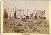 "Group of Veterans from the Battle of Little Bighorn in Front of the Custer Monument. LIBI_00081_06038; Black and white photograph size 6 1/2"" x 9"" mounted on slightly larger cardboard that is gilt-edged. The image shows a group of eight people in front of the fence surrounding the Custer monument. The names of the eight people are printed in gold at the bottom of the image. They read (top to bottom, left to right): ""Corp'l Hall, Dr. Porter, Capt Godfrey, Col. Benteen, Capt. Edgerley, Capt. McDougal, Private Penwall, Scout White Swan.""  The words ""Custer Monument."" is printed in black ink on the bottom of the card. It was produced by D.F. Barry. Dustin number: 285; picture; Courtesy of the National Park Service, Little Bighorn Battlefield National Monument, LIBI_00081_06038, D. F. Barry, ""Group of Veterans from the Battle of Little Bighorn in Front of the Custer Monument,"" date unknown"