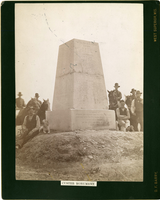 "Group of Men, Some Mounted, Around the Custer Monument. LIBI_00081_06043; Black and white photograph 6 1/4"" x 8 3/4"" mounted on heavy black cardboard with gilt-edges. Size:  8"" x 10"". This image shows a close-up of Custer monument. There are two mounted men and one man seated with a dog on the left side. On the right side, there are two mounted men, one man standing and another seated. There is a printed label below the image that reads ""Custer Monument"". It was photographed by D.F. Barry in 1886. Dustin number: 285; picture; Courtesy of the National Park Service, Little Bighorn Battlefield National Monument, LIBI_00081_06043, D. F. Barry, ""Group of Men, Some Mounted, Around the Custer Monument,"" 1886"