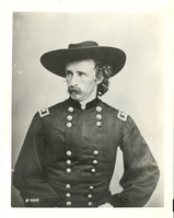 "Brevet Major General George Armstrong Custer. LIBI_00011_07098; A black-and-white photograph (reproduction print) of General George A. Custer, originally taken in 1865 by Mathew Brady. Custer is wearing a Major General's uniform. National Archives identification number in lower left-hand corner is B-4509. Reverse has typewritten script indicating Custer Rank as Brevet Major General.; PRINT, PHOTOGRAPHIC; Courtesy of the National Park Service, Little Bighorn Battlefield National Monument, LIBI_00011_07098, Mathew B. Brady, ""Brevet Major General George Armstrong Custer,"" 1865"