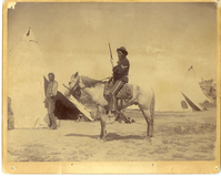 "Medicine Pipe in Cavalry Uniform Mounted on a Horse; Man Identified as Two Whistle Stands at the Door of a Sibley Tent at Fort Custer, Montana. LIBI_00263_07840; A photograph 9 1/2"" x 7 1/4"" mounted on a 10"" x 8' card.  The photograph is in fair condition. It shows a mounted Indian scout dressed in a cavalry uniform of the 1880's. He is identified on the back of the photograph as Medicine Pipe.  The background shows three Sibley tents and a male Indian with one arm tentatively identified as Two Whistle.  A handwritten note on verso reads: ""Two Whistles (?)- one armed man"", written in blue ink, and ""mont-soldier = Medicine Pipe (Big Medicine?)"" written in pencil.  The words ""killer of Proud Bear"" (presumably relating to Big Medicine) are crossed out. The words ""Fort Custer"" are written upside-down along the bottom in blue ink. The photograph was taken at Fort Custer, MT, circa 1885. It is in fair condition ; photograph;  Courtesy of the National Park Service, Little Bighorn Battlefield National Monument, LIBI_00263_07840, Unknown Photographer, ""Medicine Pipe in Cavalry Uniform Mounted on a Horse; Man Identified as Two Whistle Stands at the Door of a S"