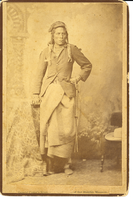 "Curly in Jacket with Blanket Wrapped Around His Waist. LIBI _00218_07060; Photo is black and white, sepia toned, mounted on card. This image depicts Curley, Custer's scout.  Curley standing full length posed as if done in a studio with right hand on a pedestal, left hand on hip.  A chair with hat on it appears to the right.  Image is faded, but clear and unscratched. A printed label pasted along the bottom mount reads ""General Custer's Scout [illegible] of that Horrible Massacre."" The verso has ""D.F. Barry Photographer, Bismarck, D.T.""  printed in red.; print, photographic; Courtesy of the National Park Service, Little Bighorn Battlefield National Monument, LIBI_00218_07060, D. F. Barry, ""Curly in Jacket with Blanket Wrapped Around His Waist,"" date unknown."