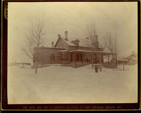 "General George Armstrong Custer's Quarters at Fort Abraham Lincoln, Covered in Snow with an Unidentified Person Standing in Front. LIBI_00019_00571; This item is an albumen, card-mounted photograph of General George A. Custer's quarters at Fort Abraham Lincoln, Dakota with an unidentified person standing in the snow in front of the building.  The imperial view photograph is 7 1/4 x 9 1/4"" (8 x 10"" mounted in a dark brown mount) and was produced circa 1880 by David F. Barry.  On the front, a typed caption in gold ink reads, ""Bismark/The late Gen. Geo. A. Custer's Quarters at Fort Abraham Lincoln, Dak.""  On the verso, a handwritten notation in pencil reads, ""G.A. Custer house - Head Quarters Fort Abraham Lincoln, Dakota.""  Handwritten description provided by Elizabeth B. Custer.Note: Bronze disease is evident.   Photograph reprinted in ""The Custer Album"" by Lawrence A. Frost, page 139.; Print, Photographic [Mounted on Card]; Courtesy of the National Park Service, Little Bighorn Battlefield National Monument, LIBI_00019_00571, D. F. Barry, ""General George Armstrong Custer's Quarters at Fort Abraham Lincoln, Covered in Snow with an Uniden"