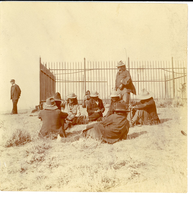 "Two Moons and Other Cheyenne Sitting in a Group at the Front of the Custer Monument on Last Stand Hill. LIBI_00263_07923; A small (3 2/8"" x 3 2/8"") photograph This image depicts a group of Native Americans seated in a group beside the Custer Monument on Last Stand Hill.  On the verso of the photograph is a note in blue ink: ""Two Moons and other Cheyenes at spot where Custer fell talking over the battle, 1905.  From collection of Major S.G. Reynolds.""  The image is in good condition, but somewhat discolored from age. This image was produced by an unknown photographer in 1905. (see accession file folder); photograph;  Courtesy of the National Park Service, Little Bighorn Battlefield National Monument, LIBI_00263_07923, Unknown Photographer, ""Two Moons and Other Cheyenne Sitting in a Group at the Front of the Custer Monument on Last Stand Hill,"" 1905."