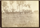 "Soldiers and Civilians, Including Ladies, at Camp Baldwin on the Custer Battlefield on the 10th Anniversary. LIBI_00081_06045; Black and white photograph 6 1/2"" x 9 1/4"" mounted on heavy maroon cardboard with gilt-edged. Size:  7"" x 10"". Image shows Camp Baldwin on the Custer battlefield, June 25, 1886. There is a row of soldiers from the left to the center of the image. A group of ladies and gentlemen are seated around a tent on the right side of the image. A large American Flag is hung from a tree branch in almost the exact center of the image. The words: ""Camp Baldwin, Custer Battlefield, June 25, 1886"" are embossed in gold foil at the bottom of the image. It was photographed by D.F. Barry. ; picture; Courtesy of the National Park Service, Little Bighorn Battlefield National Monument, LIBI_00081_06045, D. F. Barry, ""Soldiers and Civilians, Including Ladies, at Camp Baldwin on the Custer Battlefield on the 10th Anniversary,"" June 25, 1886"