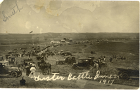 "Cars Parked at the Battlefield. LIBI_00195_06970; Black & white photo post-card. This image depicts a view of the battlefield. Cars and horses crowd the foreground. The cemetery and Superintendent's Lodge are visible in the background. The photo was taken from Custer Hill. A handwritten note in white along the bottom reads: Custer Battle, June 1917"". A pencil note in the upper left corner says: ""Smith"". The image is worn and has stains. The image was taken by an unknown photographer. ; print, photographic; Courtesy of the National Park Service, Little Bighorn Battlefield National Monument, LIBI_00195_06970, Unknown Photographer, ""Cars Parked at the Battlefield,"" circa 1917."