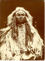 "Mars Che Coodo (White Man Runs Him) in Full Tribal Dress; Long Bust View. LIBI_00019_00582; This item is a photographic print of White-Man-Runs-Him, scout at the Battle of Little Big Horn, in long bust view and dressed in full tribal costume. The image is 5 7/8 x 7 15/16"" and was produced circa 1910 by D.L. Gee.  On the verso, a handwritten notation in pencil reads, ""7736 Sioux - Crow -  Chief Mars-che-Coodo - ""White Man Runs Him"" - Son of Pretty Eagle - U.S. Gov Scout under Gen'l Custer June 25, 1876.""  Another handwritten notation reads, ""Presented by John Wood/2114 Bank St./Baltimore, Md.""  A portion of the handwritten description provided by Elizabeth B. Custer.Photograph reprinted in ""The Custer Album"" by Lawrence A. Frost, page 166.; Print, Photographic; Courtesy of the National Park Service, Little Bighorn Battlefield National Monument, LIBI_00019_00582, D. L. Gee, ""Mars Che Coodo (White Man Runs Him) in Full Tribal Dress; Long Bust View,"" circa 1910"