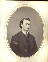 "Portrait of Thomas Ward Custer a Civilian Suite and 'C' Tie Tack. LIBI_00019_01997f ; A leather-bound photograph album, containing the individual portraits (photographic prints, with oval mats) of the graduating class of 1861, of West Point, United States Military Academy. Other photographs were possibly included.  Pencil notation reads, ""Acc. #88, see accession folders KBD 07feb1991.""  Corrected the accession back to LIBI_00019 see note to file in the accession 19 file (12/16/15 SS)Condition note: bronze disease is apparent on photographs due to gold or bronze detail of the album pages (print mats)    Formerly: Custer_Brother-WW; #648Portrait of Thomas W. Custer a Civilian Suite and ""C"" Tie Tack ; Album, Photographic; Courtesy of the National Park Service, Little Bighorn Battlefield National Monument, LIBI_00019_01997f, Unknown Photographer, ""Portrait of Thomas Ward Custer a Civilian Suite and 'C' Tie Tack,"" 1861"