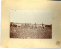 "Riders, Wagons, and Others Line Up for a Parade. LIBI_00300_10560; Black and white photo mounted on cardboard. The image depicts wagons, a buggy, and several mounted men. Custer National Cemetery and ridges of the battlefield are visible in the background. There is a large dark stain bottom right corner of cardboard and more stains throughout. A handwritten note on verso reads: ""Crow Indian Parade Custer Battlefield 1897"". The photograph was taken by Mr. Krotenberg in 1897.  ; photograph; Courtesy of the National Park Service, Little Bighorn Battlefield National Monument, LIBI_00300_10560, Krotzenberg, ""Riders, Wagons, and Others Line Up for a Parade,"" 1897."
