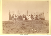 "Veterans of the Battle of the Little Bighorn and Their Wives. LIBI_00081_06047; Black and white photograph 6 1/4"" x 8 3/4"" mounted on heavy white cardboard, with gilt-edged. Total size:  7' x 10"". This image shows a group of people in front of the fence around the Custer Monument.  The names of the subjects are printed at the bottom of the image. The words: ""Custer Monument"" are printed at the bottom of the card.  Dustin number: 285; picture; Courtesy of the National Park Service, Little Bighorn Battlefield National Monument, LIBI_00081_06047, D. F. Barry, ""Veterans of the Battle of the Little Bighorn and Their Wives,"" date unknown"
