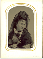 "Tintype Portrait of Elizabeth Bacon Custer in a Black Lace Veil and Holding a Cross. LIBI_00295_10707; A tintype portrait of Libbie Custer in full bust view. She wears a black lace veil, and a dress with geometric patterning. She has a black ribbon necklace. There is a large broach in the center of her collar. She holds a cross in her right hand. There is a slight tint on her cheeks. The image was taken by an unknown photographer on an unknown date. ; photograph;  Courtesy of the National Park Service, Little Bighorn Battlefield National Monument, LIBI_00295_10707, Unknown Photographer, ""Tintype Portrait of Elizabeth Bacon Custer in a Black Lace Veil and Holding a Cross,"" date unknown."