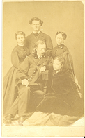 "Group Portrait of George Armstrong Custer, Elizabeth Bacon Custer, and Two Richmond Sisters. LIBI_00295_10711; An albumen card of a group portrait. The group consists of George Custer seated, surrounded by Libbie Custer, the Richmond Sister, and Charles Kendall. George Custer is wearing the uniform of the brigadier general. Charles Kendal stands directly behind custer. He is wearing civilian clothing. There is a Richmond sister on each side. Libbie sits on the floor to George's left. She is wearing a dark coat over a light colored dress. The verso has a stamp reading: ""J. Noble & Co. , photographs, 88 Delaware Street, Leavenworth, Kansas.  There are two nicks to left of Kendall's head. The image was taken on an unknown date. ; photograph;  Courtesy of the National Park Service, Little Bighorn Battlefield National Monument, LIBI_00295_10711, Jay Noble & Company, ""Group Portrait of George Armstrong Custer, Elizabeth Bacon Custer, and Two Richmond Sisters,"" date unknown."