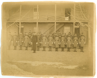 "Men in Long Jackets Holding Rifles with Fixed Bayonet in Front of a Barracks Building. LIBI_00090_05176; A [collodion] photograph, mounted on card. This image shows unidentified troops before barracks. The men wear long jackets and capes. They hold rifles with the bayonets fixed. It is possibly at Fort Custer or Fort Keogh. It was by an unknown photographer on an unknown date. The card is brittle and discolored.; print, photographic [mounted on card]; Courtesy of the National Park Service, Little Bighorn Battlefield National Monument, LIBI_00090_05176, Unknown Photographer, ""Men in Long Jackets Holding Rifles with Fixed Bayonet in Front of a Barracks Building,"" date unknown"