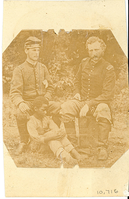 "George Armstrong Custer and James Barroll Washington with an African American Boy on the Ground Near Washington's Feet. LIBI_00295_10716; An albumen image with a canvas cut at 30 degree angles. This image depicts George Custer, James B. Washington, and a Negro boy seated on the ground between James Washington's legs. The photo is torn at the bottom center. This tear extends 1/2"" through the boy's feet. There are chips from the photo at the top between Custer and Washington's heads. There are also chips from the bottom next to the tear on the right side. A similar image appears in other collections. This image was taken by an unknown photographer on an unknown date. ; photograph;  Courtesy of the National Park Service, Little Bighorn Battlefield National Monument, LIBI_00295_10716, Unknown Photographer, ""George Armstrong Custer and James Barroll Washington with an African American Boy on the Ground Near Washington's Feet,"" date unknown."