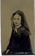 "Portrait of Elizabeth Bacon Custer in a Dark Dress and Dark Lace Veil. LIBI_00295_10693; Tintype A portrait of Elizabeth Bacon Custer is seated in left facing profile. She is wearing dark clothing with a white color and a dark lace veil. A chair back is shown to the side of Libbie's lower left. The image was taken by an unknown photographer, circa 1864. ; photograph;  Courtesy of the National Park Service, Little Bighorn Battlefield National Monument, LIBI_00295_10693, Unknown Photographer, ""Portrait of Elizabeth Bacon Custer in a Dark Dress and Dark Lace Veil,"" circa 1864"