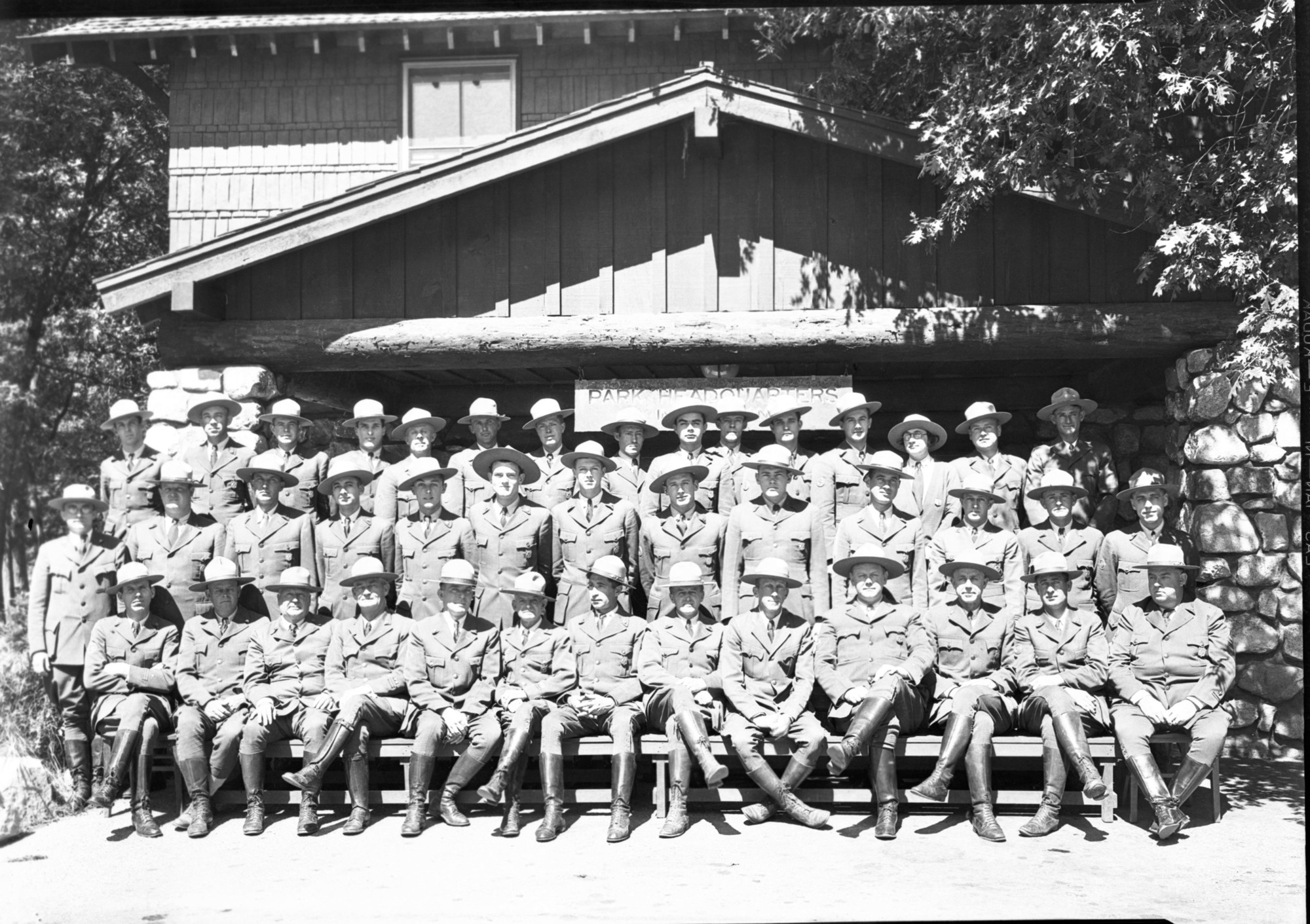 July 4th Conference of Ranger Force, in front of Admin. Building. Top Row: Frank Anderson, J. Minter, Odin Johnson, Don Bryan, Grover Caster, Vernon Lowery, Mitch Akins, Otto Brown, Holmes Miller, Ted Barnett, Gene Burns, Jack Scholl, Mrs. Hazel Whedon, Lloyd Finch, Dewey Winder. Middle Row: H. Rodeck (photogr:), Whedon, Archie Westfall, Damon Eckley, Harry During, Gerald E. Mernin, Ferd. Fletcher, L. Wieland, Russ Huse, Elwin Heller, W. K. Merrill, L. Farwell, Homer B. Hoyt. Lower Row: John Bingaman, Henry A. Skelton, Chas. F. Adair, Gus Eastman, Billy Nelson, Carl Danner, Frank A. Kittredge - NPS Chief Engineer, Supt. C. G. Thomson, Chief Ranger F. S. Townsley, Assist. Chief J. Wegner, Oscar Irwin, Ernie Reed.