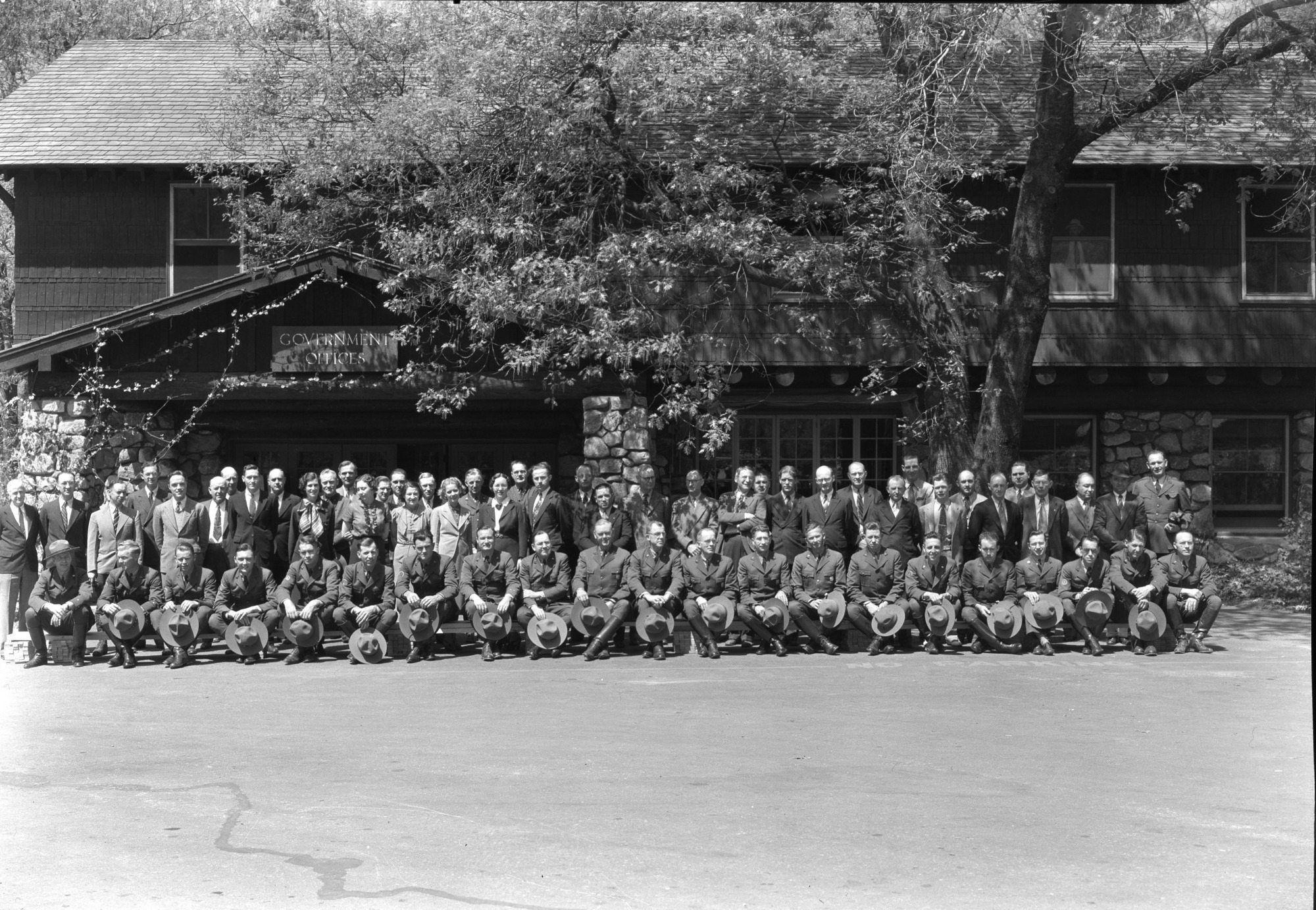 Group of permanent NPS personnel. FRONT ROW: L-R Ed Beatty, Assist. Naturalist; Frank Givens, Ranger; Duane Jacobs, Ranger; Harry During, Ranger; Lon Garrison, Ranger; John Bingaman, Ranger; Jerry Mernin, Ranger; John Wosky, Asst. Supt.; L.C. Merriam, Supt.; F.S. Townsley, Chief Ranger; John Wegner, Asst. Chief; Gus Eastman, Ranger; Carl Danner, Ranger; Vernon Lowery, Ranger; Cliff Anderson, Ranger; Homer Hoyt, Ranger; Otto Brown, Ranger; Stan Joseph, Asst. to Supt.; Jim Stakel, Ranger; Art Holmes, Ranger; Ralph H. Anderson, info. clerk & photographer; STANDING: Frank Ewing, Employment Mgr.; Russell Sprinkel, Chief Clerk; E.M. Hilton, Park Engineer; Dwight Humphries, Clerk Steno.; Jim Harrison, Sec. to Supt.; Dan Cookson, electrician; Lee Rust, road maint.; Art Guinn, Accounting, personnel (?); Harvey Ashworth, electrician; Hazel Adams, steno; Art Moen, warehouse; Henry Listina, equip. whse.; Eliz. Godgrey, sec. Museum; R. Hodges; Walt Gann, electrician; Essie Kimball, file clerk; Joe Jenkins, chief electrici